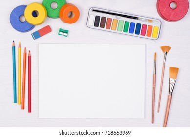 Blank piece of paper with colorful pencils, brushes and watercolors on kid's desk, top view with copy space