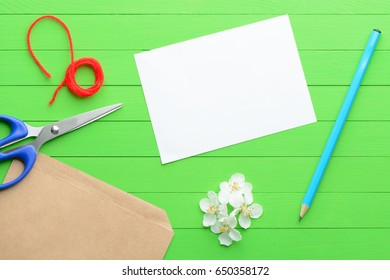A blank piece of paper with an envelope on green wooden background