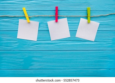 Blank pieces of note paper and colored clothespins isolated on blue. Three squares of blank paper, pegged to a string washing line, with wood plank fence in the background. Space for text.