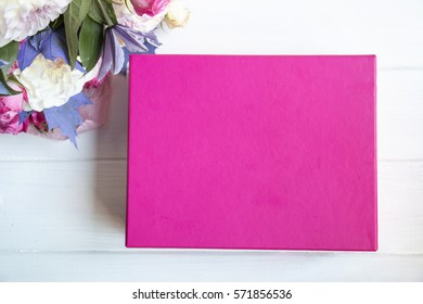 Blank pink box with flowers on white wooden background. Package box for branding.Top view