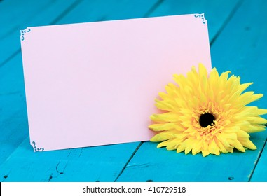 Blank pink note card by yellow sunflower on antique rustic teal blue wood background