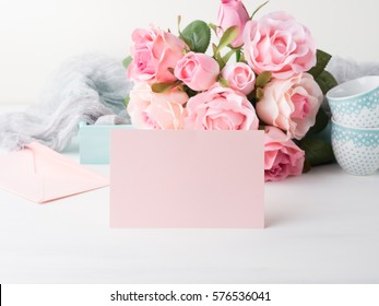 Blank pink paper card for Valentine's or mother woman day. Wedding baby birthday romantic date invitation. Background with roses tray romantic textile and two coffee cups