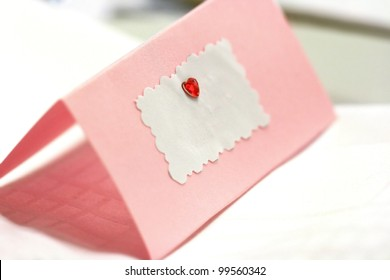 Blank pink wedding / greeting card with a red heart and copy space for text.