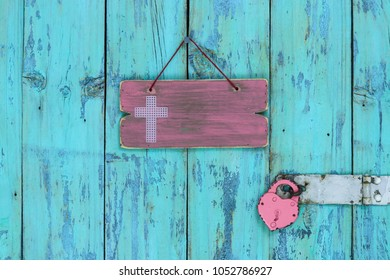 Blank pink wood sign with religious cross by heart lock hanging on rustic antique teal blue wooden door;  Easter and Memorial Day holiday concept with copy space