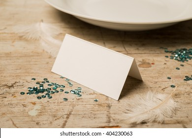 Blank place card along with green sequins, feathers, and dinner plate on a wooden surface for copy space.