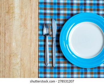 Blank plate with fork and knife on checked tablecloth and wooden table background