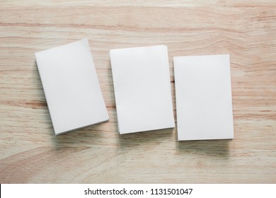 Blank portrait mock-up paper. brochure magazine isolated on brown wooden table, changeable background / white paper isolated on wood