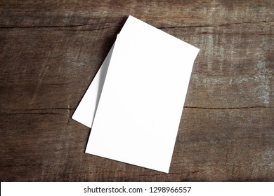 Blank portrait mock-up paper. brochure magazine isolated on brown wooden, changeable background / white paper isolated on wood