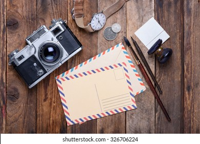 Blank post card with envelope and vintage camera, stamps, watch, ink pen and brush on wooden table still life
