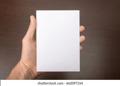 Blank postcard in hand on a gray background. Leaflet A6 mockup