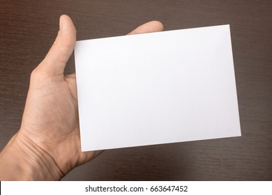 Blank postcard in hand on wooden background. Leaflet A6 mockup