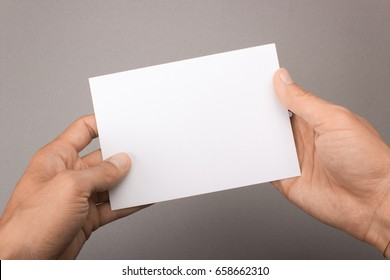 Blank postcard in hands on a gray background. Leaflet A6 mockup