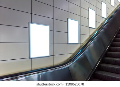 Blank poster mockup in metro station. Four big vertical / portrait orientation blank poster with metro escalator background.