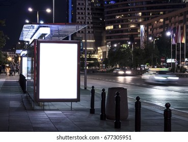 Blank poster on bus stop at night. Copy space. In background out of focus street, cars, buildings.