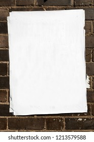Blank poster texture, crumpled, creased curled at the edges pasted on to a brick wall on top of many layers of paper.