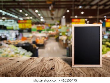 Blank price list board on wooden top table with blurred of supermarket background