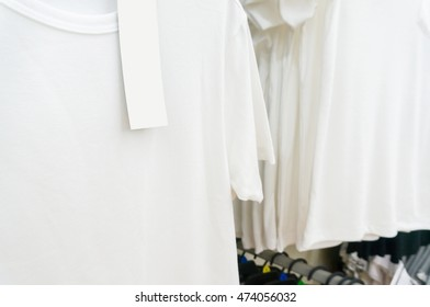 blank price tag hang over white tshirt on Hanger Shelf in Supermarket or Hypermarket Retail Store Outlet, Shallow Depth of Field.