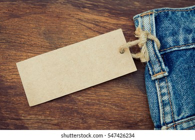 Blank price tag hanging on denim jean with rustic wooden style background in vintage tone
