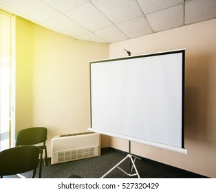 Blank projector canvas in the office seminar meeting room with beautiful sun passing through the window