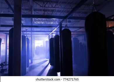 Blank punching bags in misty cinematic boxing gym and film set.