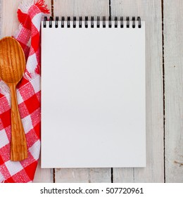 Blank recipe book on a wooden table with a red and white napkin and a wooden spoon, square