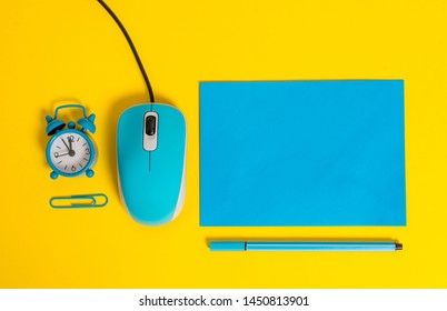 Blank rectangular paper sheet metal alarm clock wakeup clip binder pencil marker computer wire mouse gadget colored background Empty text important events
