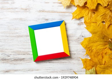 Blank rectangular photo frame lies on vintage wooden desk with bright autumn foliage. Flat lay with autumn leaves on white wooden surface. Simple colorful picture frame with copy space for design.