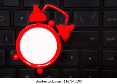 Blank red alarm clock, black keyboard, dark laptop