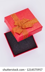 Blank red gift box isolated. Beautiful present box with golden bow. Gift box for jewelry.
