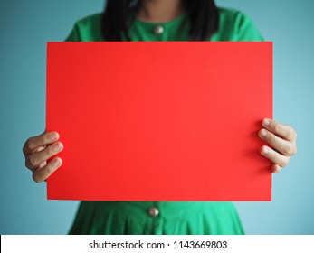Blank red paper in hands of young woman wearing green vintage dress on blue background for messages or copy space e.g. Merry Christmas!, HAPPY NEW YEAR 2019, Congratulations!, ON SALE, SHOP NOW!