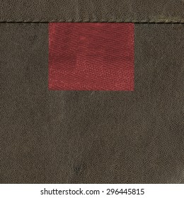 blank red textile tag on brown  leather background