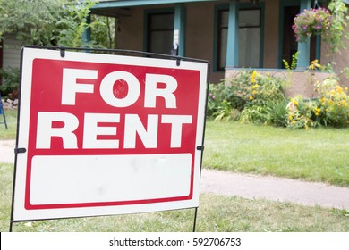 Blank for rent sign posted in the front yard of a home with porch