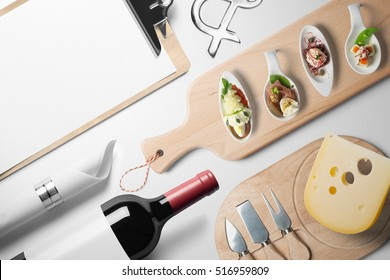 Blank restaurant menu template, on white table with wine bottle canapes and cheese, top view.