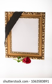 blank retro gold mourning frame with red rose on bright background for funeral card
