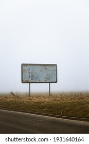 Blank ripped billboard on the edge of the road on the field that has apocalyptic vibe, because of the mist and moody background.