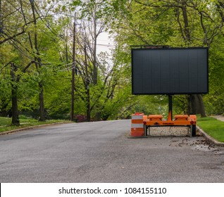 Blank road warning information sign on trailer with LED face on suburban neighborhood street lined with trees