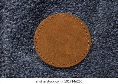 Blank round circular leather label sewn on fleece fabric, macro close up