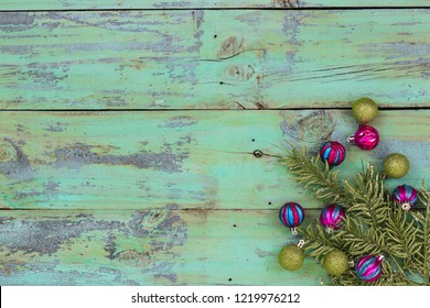 Blank rustic antique mint green wood sign with Christmas tree garland and teal blue and pink ornaments; holiday background with painted copy space