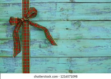 Blank rustic antique teal blue wood sign with red and green plaid Christmas bow border; holiday background with aged painted copy space