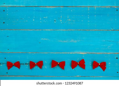 Blank rustic antique teal blue wood sign with red Christmas bows border; holiday background with painted wooden copy space