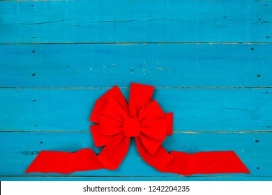 Blank rustic antique teal blue wood sign with large red Christmas bow border; holiday background with painted wooden copy space