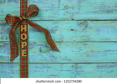 Blank rustic antique teal blue wood sign with red and green plaid Christmas bow border and the word HOPE; holiday background with aged painted copy space