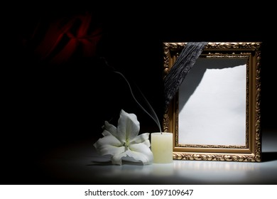 Blank rustic golden picture  frame, with smoky candle and white lily flower on dark background with red decoration