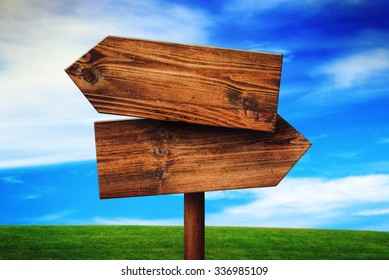 Blank Rustic Opposite Direction Wooden Sign on Grassland Field, Concept of Choice, Choosing Your Life Path.