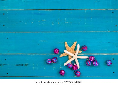 Blank rustic teal blue wood holiday sign with starfish and pink and turquoise Christmas ornaments; painted wooden  background with copy space