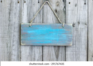 Blank rustic teal blue wooden sign hanging on old weathered wood background