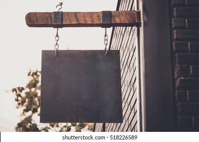 blank rusty metal hanging on wood bar for shop, vintage tone