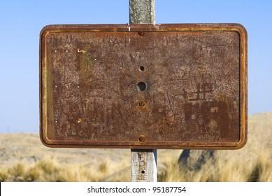 A blank rusty sign in a arid region