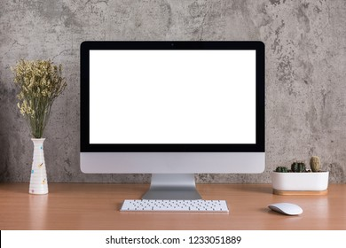 Blank screen of all in one computer with dry flowers and cactus vase on raw concreate background