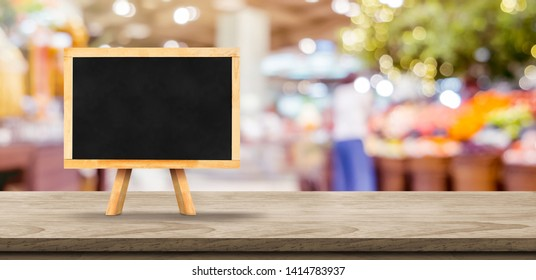 Blank screen blank blackboard on wooden table top with blur supermarket grocery bokeh background,Mock up for display or montage of design